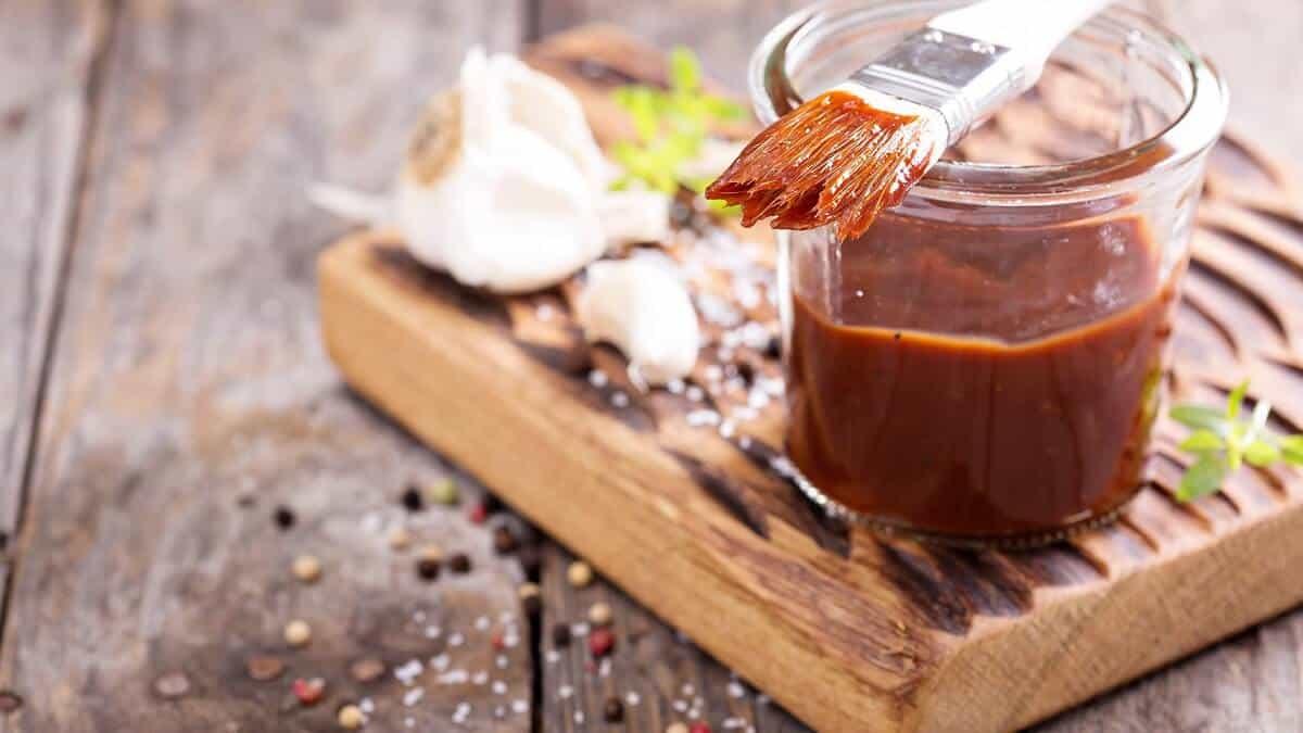 BBQ saus in een glazen pot op een houten dienblad